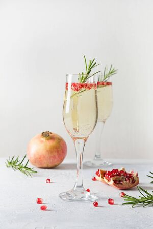 Two glass of Pomegranate Christmas holiday cocktail with rosemary sprig, sparkling wine, club soda on white table. Xmas drink. Close up.
