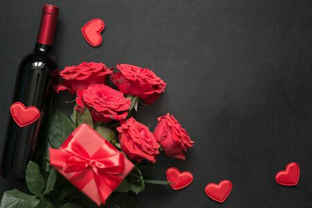 Bouquet of red roses, gift, bottle of red wine on black table. Top view with space. Stock Photo - 137499772