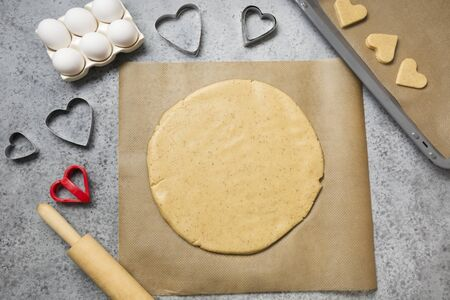 Process of making homemade cookies for St. Valentines Day on grey stone table. View from above.