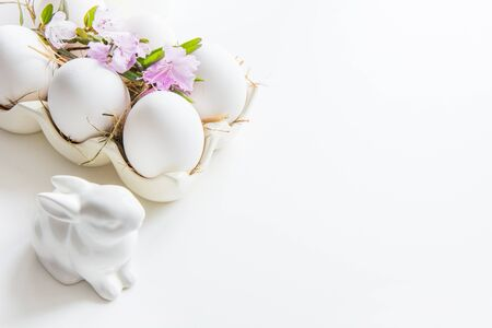 Organic white chicken eggs with spring fresh flowers in porcelain box. Easter. Close up. Copy space.