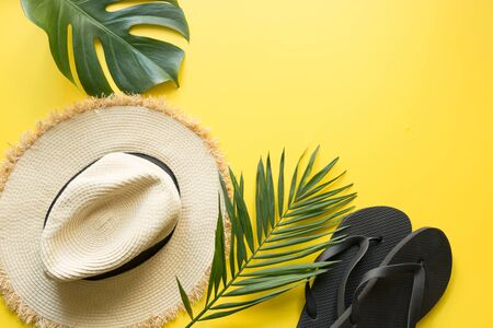 Beach straw sun hat, flip flops and monstera leaves. Summer holiday background with accessories on yellow. View from above, flat lay. Space for text. Reklamní fotografie