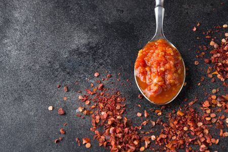 Traditional adjika hot chili pepper sauce paste harissa in spoon on black. Tunisia, georgian and arabic cuisine. Close up. Space for text.