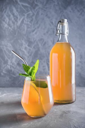 Kombucha healthy drink in bottle and glass garnish mint. Vertical format. Organic probiotic drink.