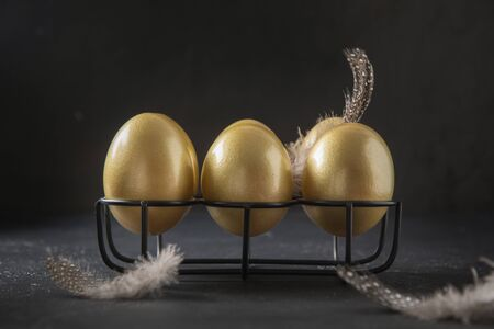 Chicken golden eggs in stand decorated feathers on black background. Easter dark concept. Close up.