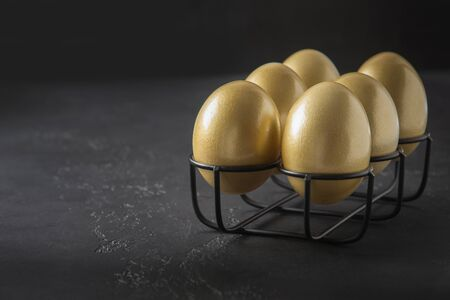 Chicken golden eggs in stand on black background. Easter dark concept. Close up. Copy space. Banco de Imagens