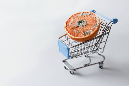 Moldy orange in grocery cart. Problem of spoiled products in store. Incorrect storage food. Close up. Copy space. Reklamní fotografie