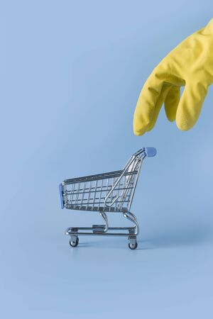 Yellow gloved hand reaches for trolley cart on blue table. Hygiene in store. Concept of shortages of essential commodities in Coronavirus time.