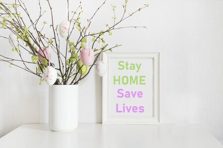 Easter concept 2020. Vase with birch tree branches with pastel eggs eggs and frame for Easter eggs and frame with slogan - Stay at Home, Save Lives.