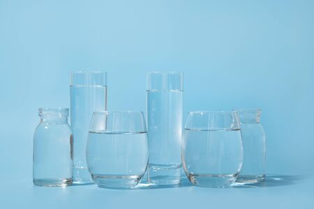 Glasses with clean water in different shapes on blue. Concept of benefits of clean and fresh water. Daily rate. Norm of day for healthy and detox. Water balance.