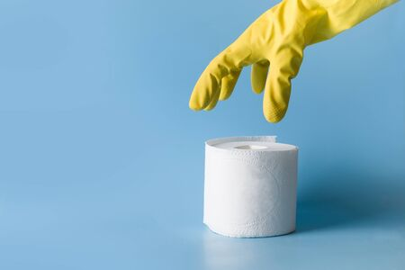 Yellow gloved hand reaches for roll of white toilet paper on blue table. Vertical shot. Concept of shortages of essential commodities in Coronavirus time. Pandemic COVID-19.