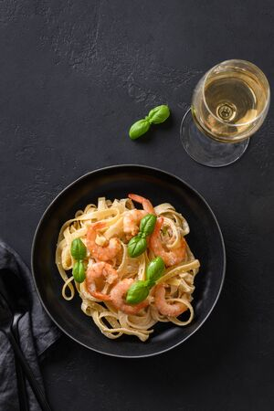 Italian pasta fettuccine with shrimps and glass of white wine on black table. Vertical shot.