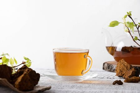 Chaga mushrooms beverage in glass cup on white. Trendy healthy drink. Close up. Useful coffee alternative to boost immunity. Standard-Bild