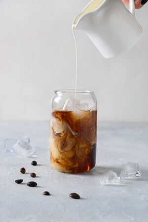 Iced latte coffee in glass with pouring milk on light background. Vertical format. Close up.