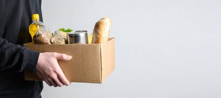 Volunteer holding donation food with goods. Box with oil, vegetables, canned food, cereals, fruits. Delivery food. Banner with copy space