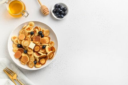 Tiny trendy pancakes with blueberry and honey on white table. View from above. Tasty breakfast. Copy space.