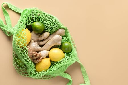 Green mesh bag with healthy food, lemon, lime, ginger, turmeric on beige.View from above. Stocks of products to strengthen immunity from virus. Фото со стока