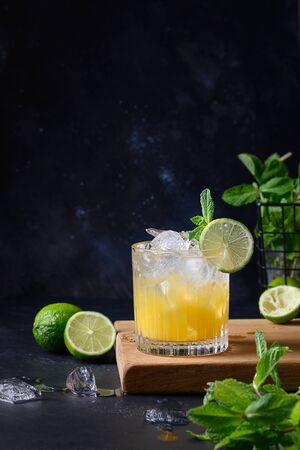Freshness tropical lemonade with lime, orange, ice cube and mint on black. Vertical format. Stock Photo