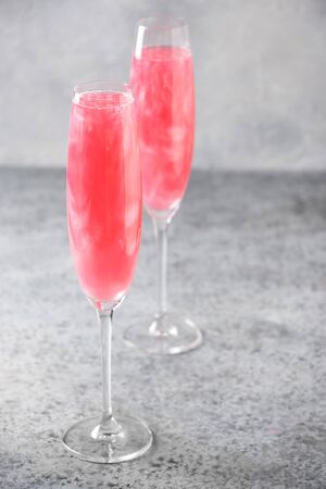 Two glasses of sparkling rose wine with shimmer glitter garnish rosemary on grey table. Romantic party for couple 写真素材