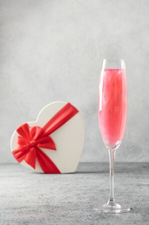 Shimmer edible glitter sparkling wine in two glasses with gift shaped of heart on grey. Close up.