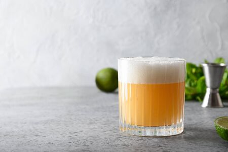 Pisco sour cocktail - whiskey with lime, egg white, sugar syrup in glass on grey stone table. Space for text. Standard-Bild