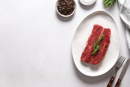 Raw marbled ribeye steak with rosemary on white. Top view. Space for text.