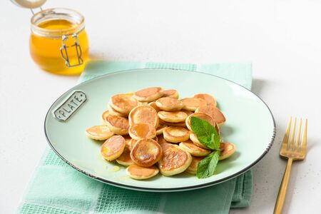 Homemade tiny cereal pancakes dressing mint with honey on white table. Close up. Reklamní fotografie