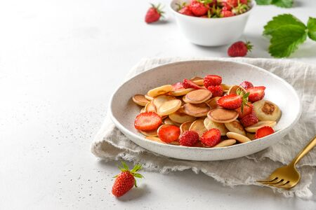Trendy summer breakfast with mini pancakes and fresh strawberry on white table. Copy space. Close up.