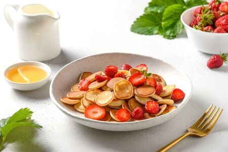 Trendy summer breakfast with mini pancakes and strawberry on white table. Close up.