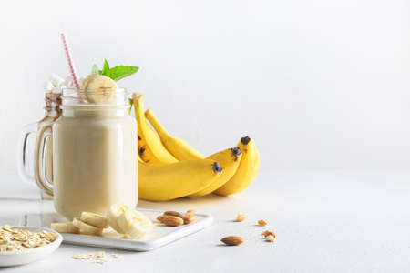 Healthy banana milkshake in mason jar on white. Tasty vegan beverage. Copy space.