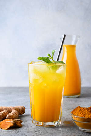 Golden freshness turmeric iced beverage garnish mint. Close up.