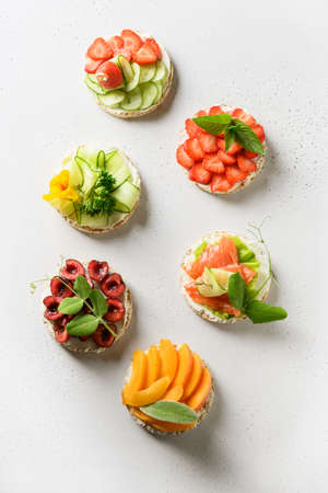Puffed rice cakes with different toppings friuts and vegetables on white background, flat lay. Vegan snacks. Vertical format.