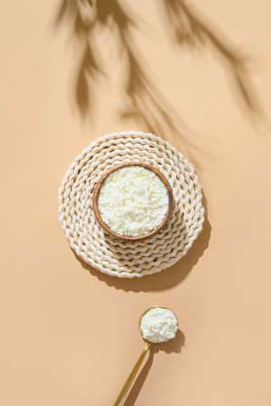 Collagen powder in wooden bowl and spoon on beige natural background with shadow. Natural beauty and health supplement. Flatlay, top view.