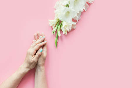 Womans hands with green manicure and white gladiolus flowers on pastel pink background. Top view. Space for text. Stok Fotoğraf