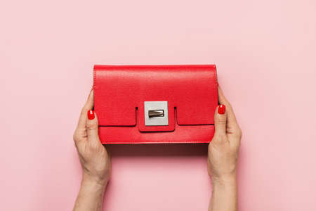 Woman hands with red manicure holding red evening clutch on pink. View from above. Stok Fotoğraf