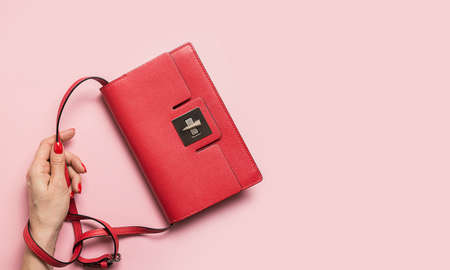Red evening clutch bag in hand on pink. Holiday banner with space for text. View from above. Creative concept.
