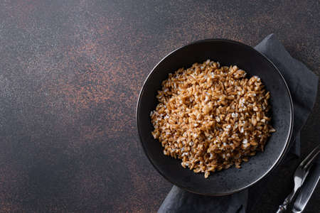 Wholegrain spelt in black bowl on brown background. Top view.