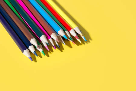Colorful pencils for draw and study in school. Bright school supplies on yellow background.