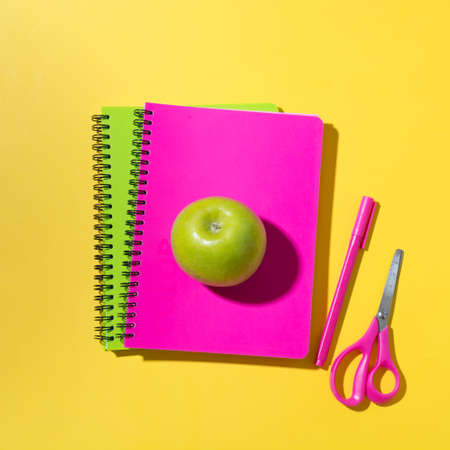 School bright supplies, notebooks, scissors, apple on yellow background. Top view, flat lay.