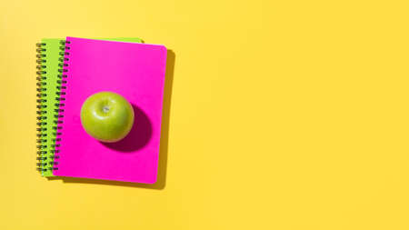 Banner with school supplies, notebooks, green apple on yellow background. Top view with copy space.