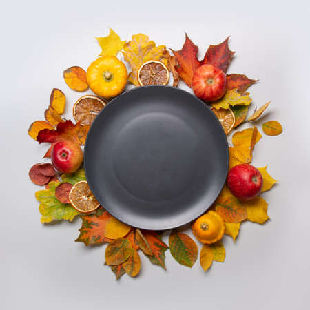Fall harvest of apple and colorful leaves and black plate in the center with space for text. View from above.