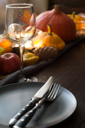 Place setting with pumpkins, autumn harvest, maple leaves. Thanksgiving Day. Close up. Vertical format.