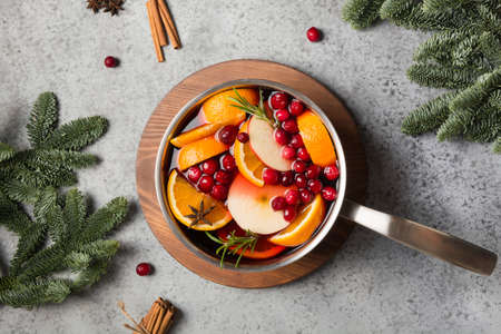 Mulled wine with cranberry, orange, rosemary spig in ladle. View from above.