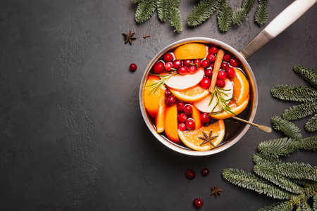 Mulled wine with cinnamon, cranberry, orange, rosemary on black stone table. Winter warming drink. Top view. Space for text.