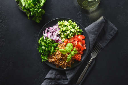 Salad of whole grain cereal spelt with seasonal vegetables, tomato, cucumber, greens in bowl on dark background. Top view. Stok Fotoğraf