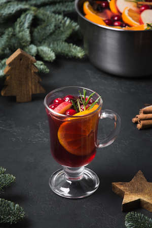 Mulled wine in glass with orange garnish rosemary sprig. Christmas holiday traditional beverage. Vertical format.