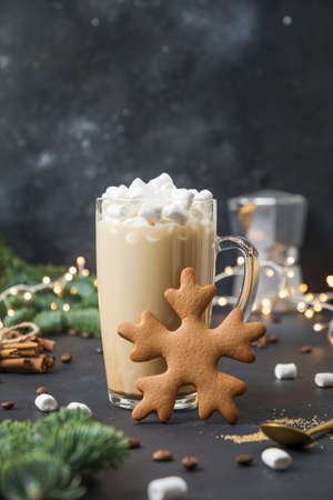 Christmas coffee with marshmallow and gingerbread shape of snowflake on dark background decorated garland. Xmas and New Year.