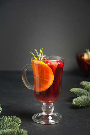 Mulled wine in glass garnish rosemary sprig. Christmas holiday traditional beverage. Vertical shot. Close up. Stok Fotoğraf