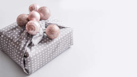 Banner of Christmas sustainable gift decorated pastel silver balls on grey. Xmas greeting card. Stok Fotoğraf