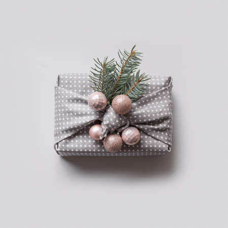 Christmas one eco gift in textile decorated natural fir tree and balls. Sustainable gifts. Furoshiki style. View from above.