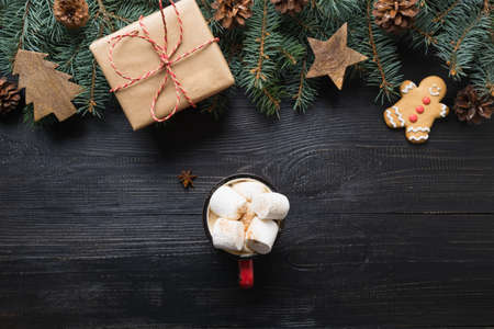 Christmas gift, coffee, marshmallow, wooden diy, evegreen fir tree on dark wooden board. Top view. Xmas vibes. Stok Fotoğraf